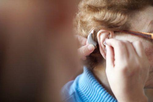 Personne âgée atteinte de presbyacousie qui essaye un appareil auditif