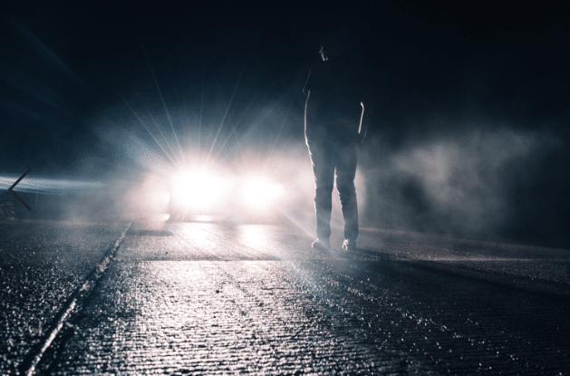 Homme qui se tient devant une voiture avec les phares allumés
